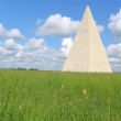 Pyramid worth on a green field — Stock Photo