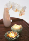 Two candles and flower on the wooden table — Stock Photo