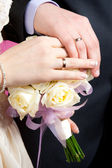 Hands of the groom and the bride lie on — Stock Photo