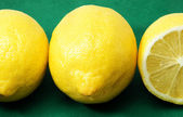 Three lemons on a green background — Stock Photo