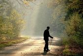 Older man through the country road — Stock Photo