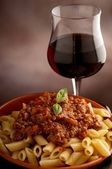 Ragu pasta and glass of wine — Stock Photo