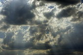 Sun appearance through dark clouds — Stock Photo