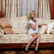 Flirting maid sitting on a sofa in hotel — Stockfoto