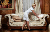 Attractive maid making a sofa in hotel — Stock Photo
