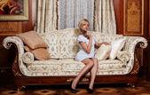 Flirten meid zittend op een bank in het hotel — Stockfoto