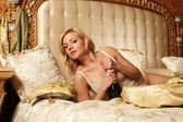 Young beautiful woman lying on a bed — Stock Photo