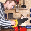 Workman with handsaw — Stock Photo