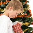Boy opening christmas present - Stock Photo