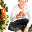 Young boy holding christmas present — ストック写真
