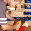 Stock Photo: Young carpenter cutting