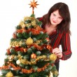 Young woman decorating christmas tree — Stockfoto