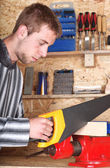Young male sawing — Stock Photo