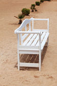 White bench in sand — Stock Photo