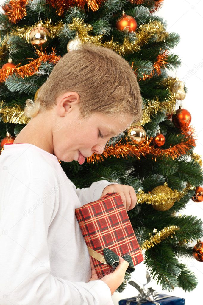 Young boy opening Christmas present near Christmas tree, studio shot — Stock Photo #1881196