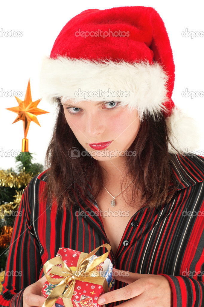 Portrait of disappointed young woman holding Christmas gift, studio shot — Stock Photo #1882695