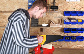Young workman with handsaw — Stock Photo