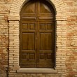 Wooden door in stone archway — Stock Photo