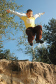 Boy jumps above the chasm — Stock Photo