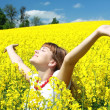 Relaxing girl in the rapeseed field - Stock Photo