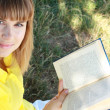 Stock Photo: Pretty young girl reading a book
