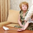 A doctor measures arterial pressure by senior lady. — Stock Photo