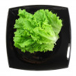 Royalty-Free Stock Photo: Leaf of lettuce on black plate . Isolated over white