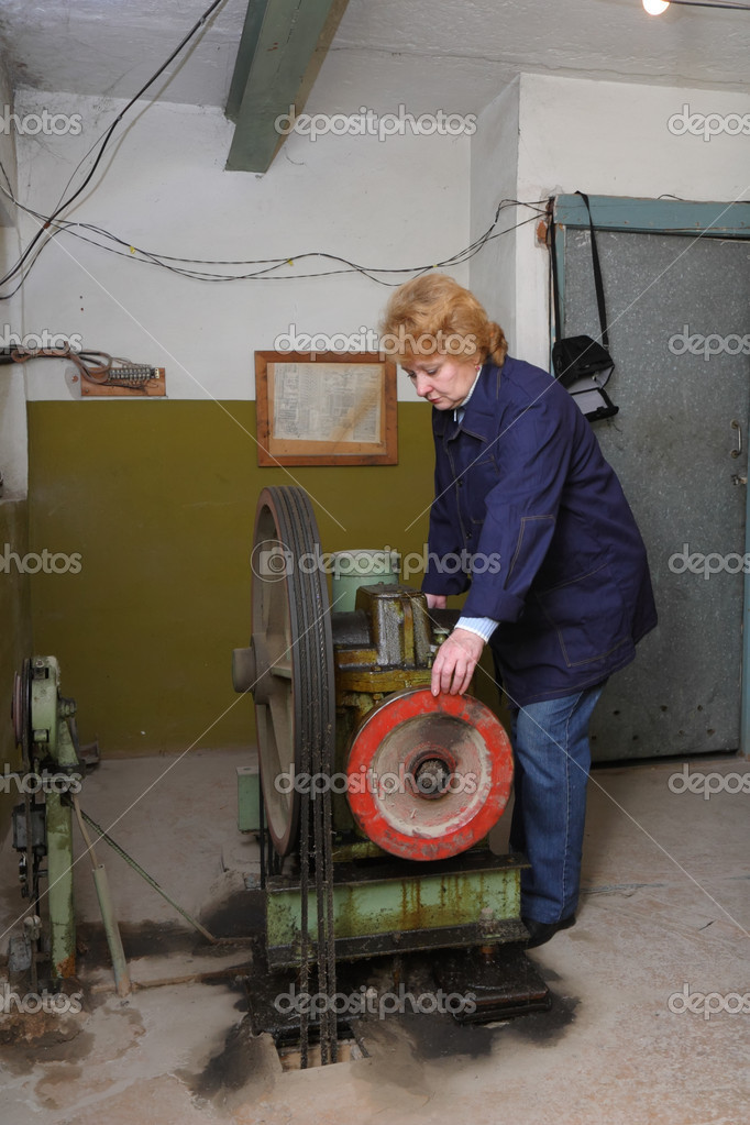 Operator woman-engineer in machine room (elevator) check the mechanical equipment. — Stock Photo #1897983