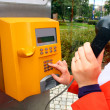 Стоковое фото: Womis using public telephone