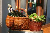 Korgar med flaskor vin och sallader — Stockfoto