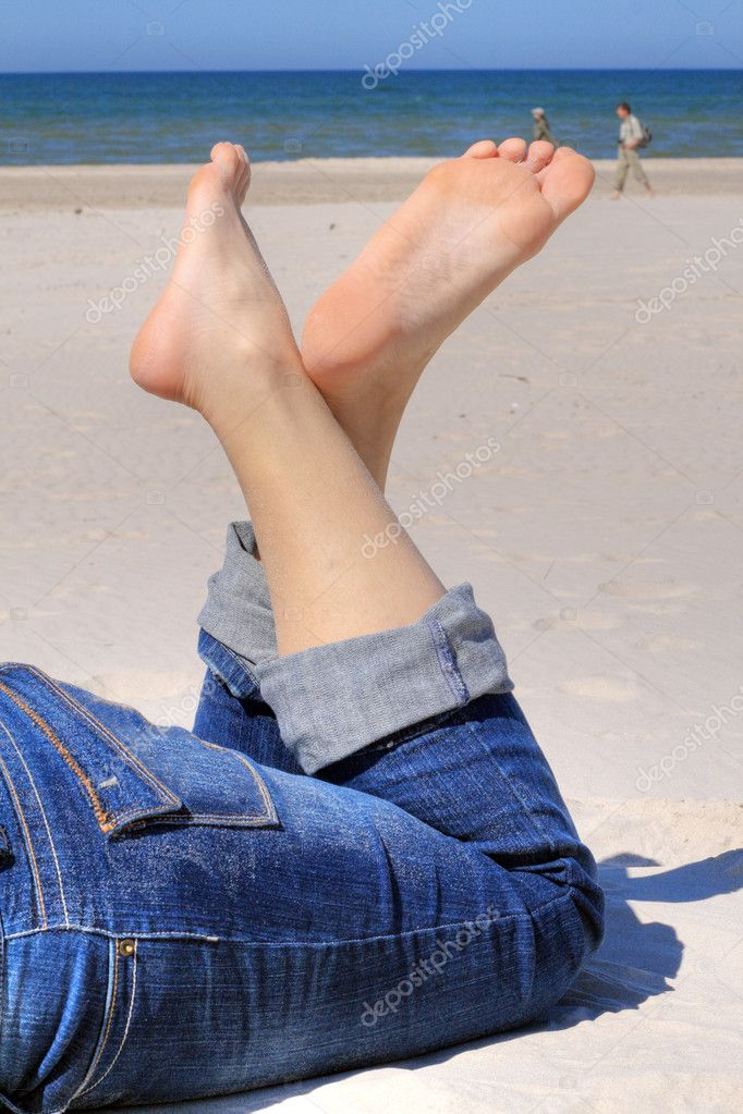 Woman in jeans with crossed legs resting on the beach — Stock Photo #1889181
