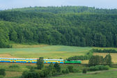 Passenger train passing through countrys — Stock Photo