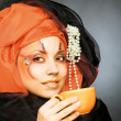 Stock Photo: Young woman in black and orange turban