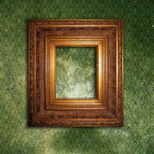 Golden frame over grunge green wallpaper — 图库照片