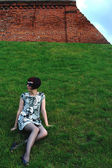 芝生の上に座っている若い幸せな女の子 — ストック写真