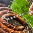 Foto Stock: Sausages roasting: grilling