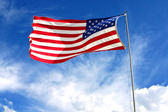 American flag on blue sky — 图库照片