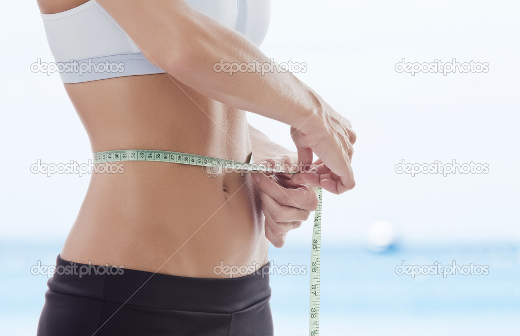 Close up view of young beautiful woman measuring her waist — Stock Photo #2429907