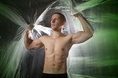 Gespierde sexy man op abstracte achtergrond — Stockfoto