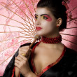 Sexy young geisha holding an umbrella — Stock Photo