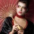 Beautiful  geisha holding umbrella - Stock Photo