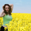 Attractive young woman in rape flower fi - Stock Photo