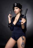 Sexy police woman holding a gun — Stock Photo