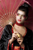 Beautiful geisha holding umbrella — Stok fotoğraf