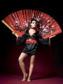 Beautiful geisha with a big fan — Stock Photo