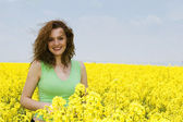 Young woman laughing in the rape flower — Stock Photo