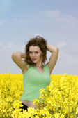 Seductive young woman in rape flower fie — Stock Photo