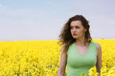 Lonely young woman in rape flower field — Stock Photo