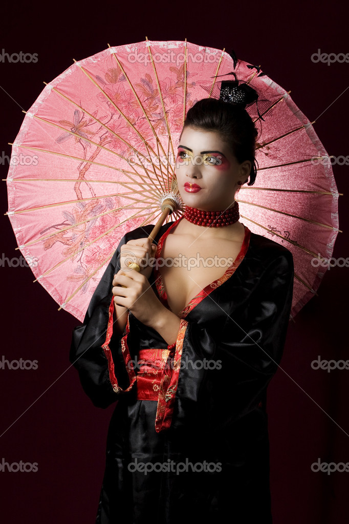 Sexy geisha wearing a traditional kimono and holding an umbrella — Stock Photo #1897908
