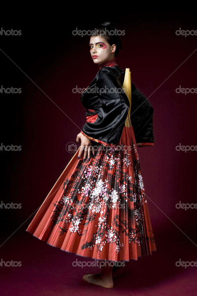 Studio shot of a beautiful geisha covering herself with a big fan — Stock Photo #1897990